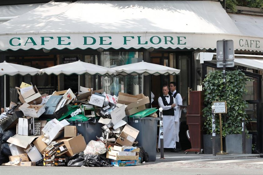 A waiter stands near a pile of rubbish bags in front of the Cafe de Flore in Paris during a strike of garbage collectors and sewer workers of the city of Paris to protest the labour reforms law proposal, France, June 8, 2016.