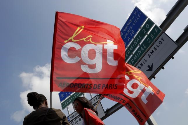 Striking employees of Roissy airport hold French CGT labour union flags during a demonstration against the labour reforms law at the Charles de Gaulle International Airport in Roissy, near Paris, France, June 7, 2016.