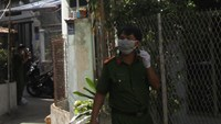 Police officers at a house where the bodies of two Ukrainian nationals were found in Nha Trang
