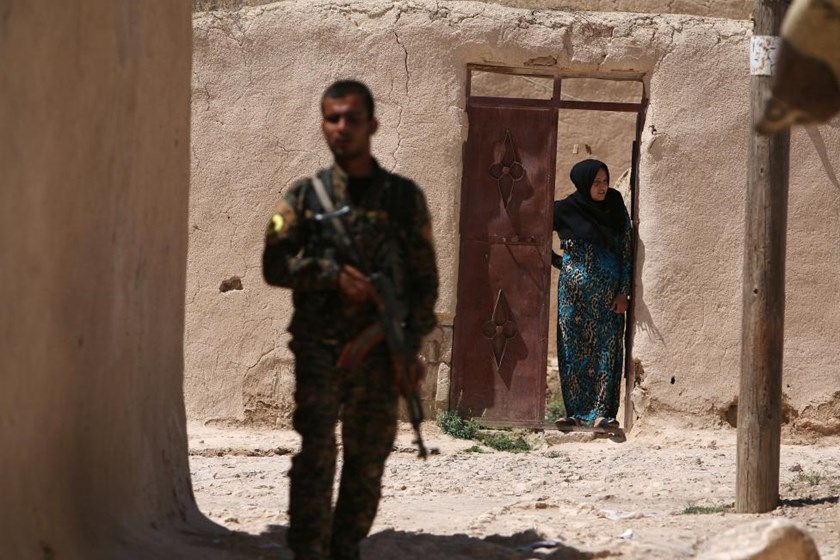 A Syria Democratic Forces (SDF) fighter stands near a woman looking out a doorway in a village, on the outskirts of Manbij city, after they took control of it from Islamic State forces, Aleppo province, Syria June 8, 2016.