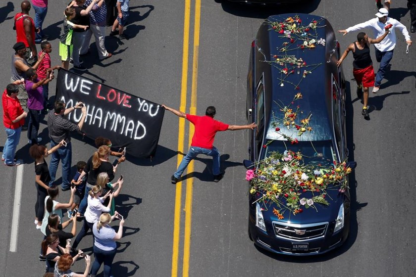 A banner stating 'We Love You Mohammad' is displayed as well-wishers touch the hearse carrying the body of the late boxing champion Muhammad Ali during his funeral procession through Louisville, Kentucky, U.S., June 10, 2016.