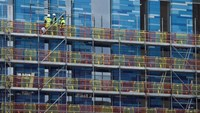 Workers stand on scaffolding on a new residential building at Battersea in London, Britain