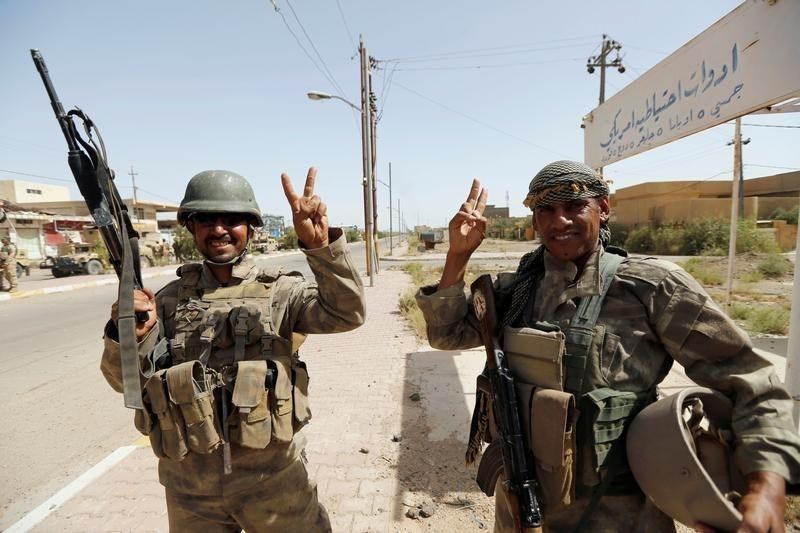 Iraqi soldiers gesture in center of Falluja, Iraq, June 17, 2016.