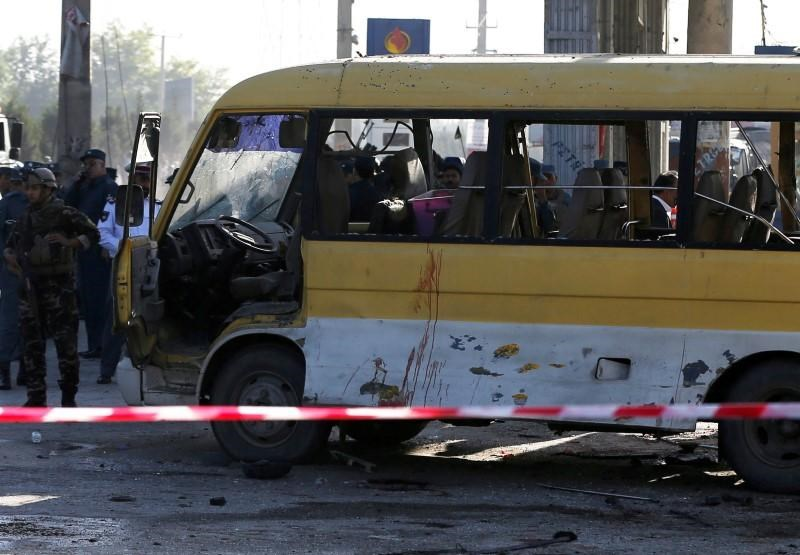 Afghan security forces inspect the damage of a minibus that was hit by a suicide attacker at the site of the incident in Kabul, Afghanistan June 20, 2016.