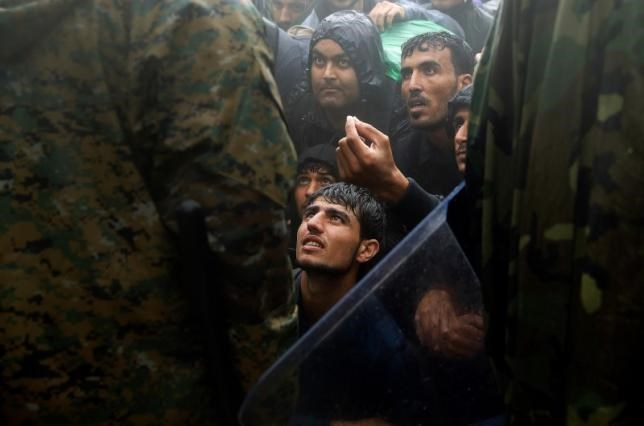 Migrants and refugees beg Macedonian policemen to allow passage to cross the border from Greece into Macedonia during a rainstorm, near the Greek village of Idomeni, September 10, 2015.