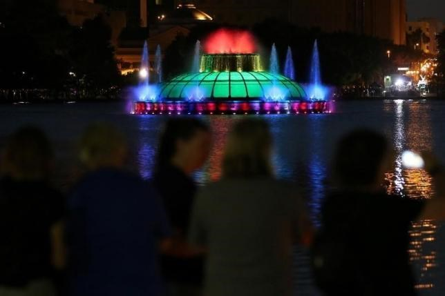 People take part in a vigil for the Pulse night club victims as the Lake Enola fountain is lit in rainbow colors following last week's shooting in Orlando, Florida, U.S., June 19, 2016.