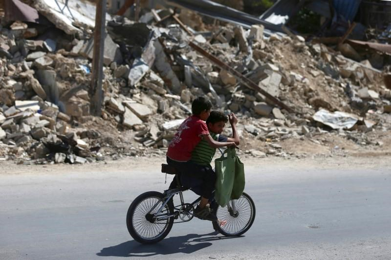 Boys ride a bicycle near rubble of damaged buildings, in the rebel held besieged town of Douma, eastern Damascus suburb of Ghouta, Syria June 10, 2016.