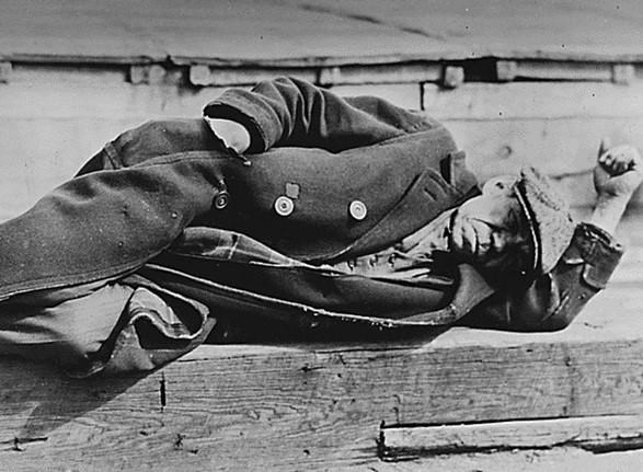An unemployed man in an old coat is seen lying down on a pier in the New York City docks during the Great Depression, 1935. REUTERS/Lewis W Hine/Franklin D. Roosevelt Presidential Library and Museum/National Archives and Records Administration/Handout/File Photo