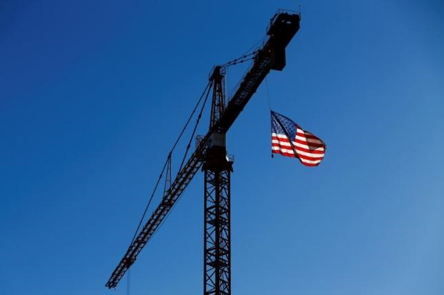A crane flies an American flag over a construction site in downtown Los Angeles, California in this October 29, 2014 file photo.