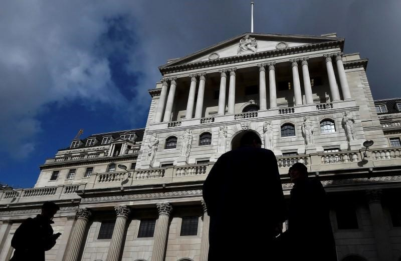 City workers walk past the Bank of England in the City of London, Britain, March 29, 2016.