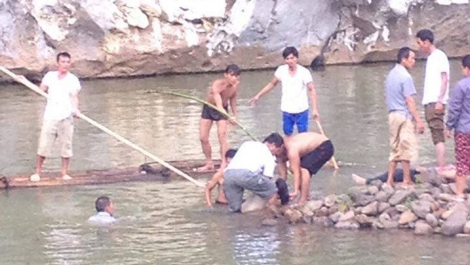 Local authorities and residents search for four students missing in the river. Photo: Vu Minh