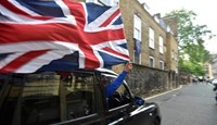 A taxi driver holds a Union flag, as he celebrates following the result of the EU referendum, in central London, Britain June 24, 2016.