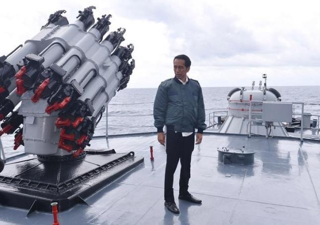 Indonesian President Joko Widodo stands on the deck of the Indonesian Navy ship KRI Imam Bonjol