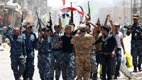 Members of Iraqi police forces celebrate on a street on June 27, 2016 in western Fallujah, 50 kilometres (30 miles) from the Iraqi capital Baghdad, after Iraqi forces retook the embattled city from the Islamic State group