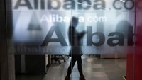 An employee is seen behind a glass wall with the logo of Alibaba at the company's headquarters on the outskirts of Hangzhou, Zhejiang province.