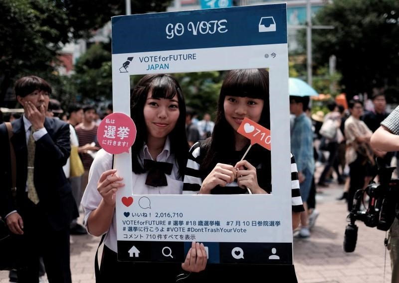 High school students pose for photos with a cardboard Instagram frame calling on youths to vote in the July 10 upper house election, in front of a busy crossing in Shibuya district in Tokyo, Japan June 26, 2016. Picture taken June 26, 2016.