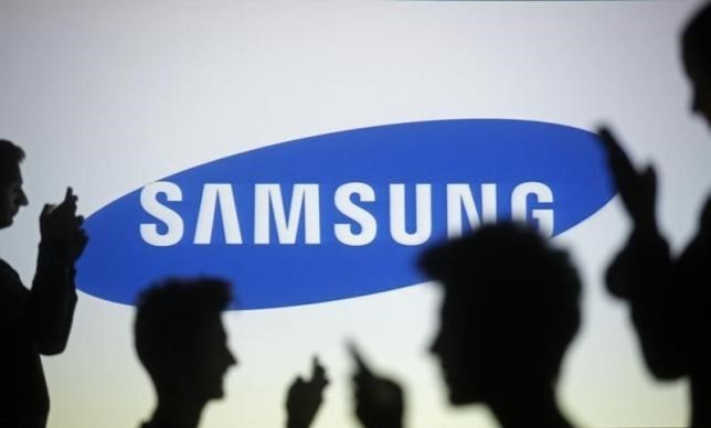 People are silhouetted as they pose with mobile devices in front of a screen projected with a Samsung logo. Photo: Reuters