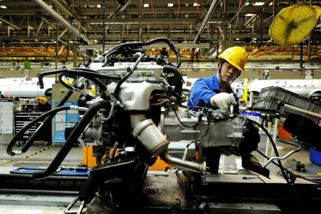 An employee works on an assembly line producing automobiles at a factory in Qingdao, Shandong Province, China, March 1, 2016.