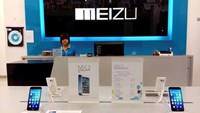 A shop assistant waits for customers at a Meizu store as Meizu MX3 smartphones are seen on display in the foreground, in Shenzhen, Guangdong province June 16, 2014.