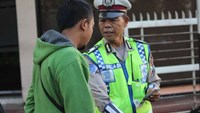 Indonesian policeman Seladi (right) speaks to a motorist in Malang, East Java, on May 18, 2016.
