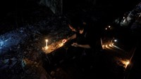 A woman lights a candle at the site after a suicide bombing in the Karrada shopping area, in Baghdad, Iraq July 3, 2016.