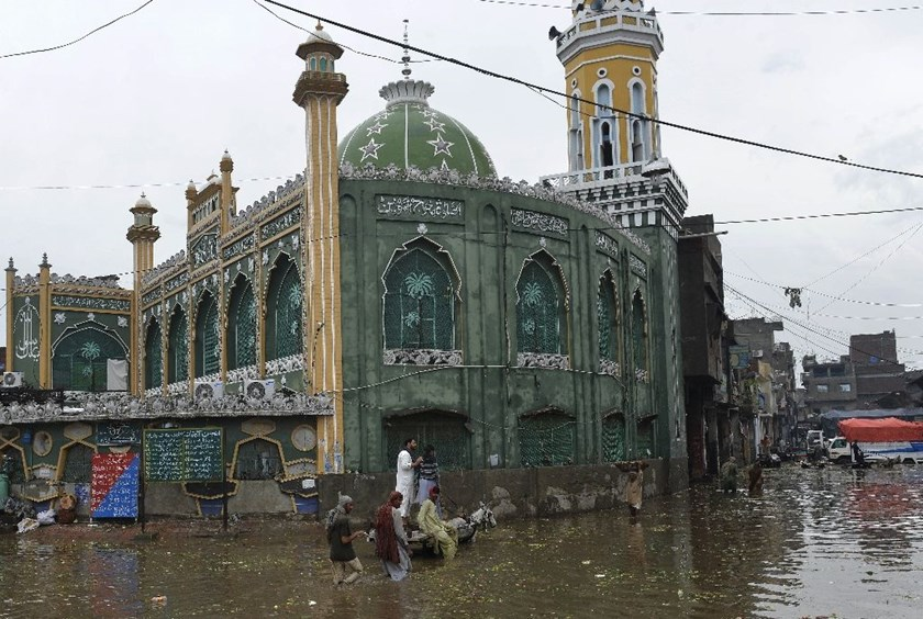 Pakistani labourers wade through flood water following heavy rain in Lahore