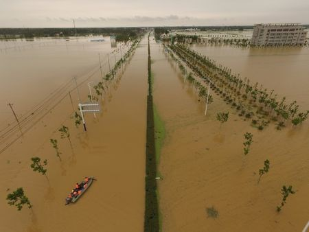 Rescuers take a boat to check around at a flooded road in Shucheng, Anhui Province, China