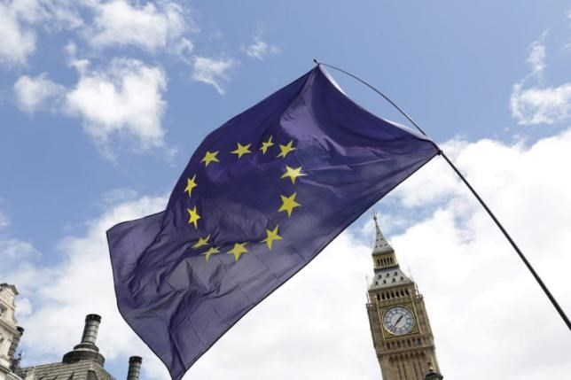A European Union flag is held in front of the Big Ben clock tower in Parliament Square during a 'March for Europe' demonstration against Britain's decision to leave the European Union, central London, Britain July 2, 2016.