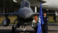 A Polish army member hods the NATO flag in front of a F-16 aircraft