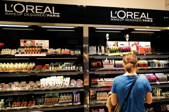 A woman stands in front of a sales display counter of French cosmetics group L'Oreal at a department store in Paris April 20, 2015.
