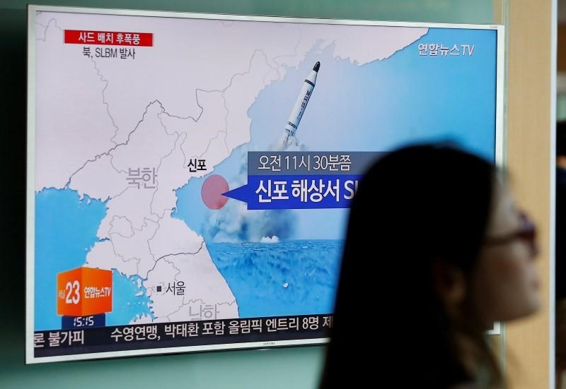 A passenger walks past a TV screen at a railway station in Seoul, South Korea, broadcasting a news report on North Korea's submarine-launched ballistic missile fired from North Korea's east coast port of Sinpo July 9, 2016.