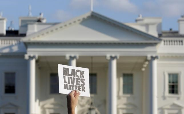 A demonstrator with Black Lives Matter holds up a sign during a protest in front of the White House in Washington, U.S., July 8, 2016.