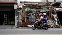 Motorcyclists ride past a house damaged by Typhoon Nepartak, in Taitung, Taiwan July 9, 2016.