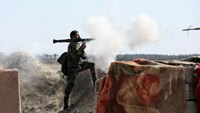 An Iraqi soldier launches a rocket-propelled grenade towards Islamic State militants
