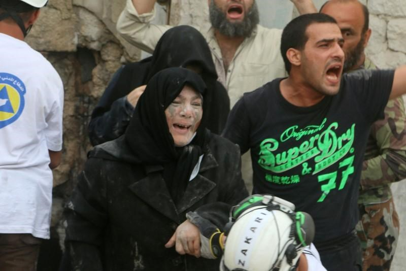 An injured woman reacts after an airstrike on Aleppo's rebel held Kadi Askar area, Syria July 8, 2016.