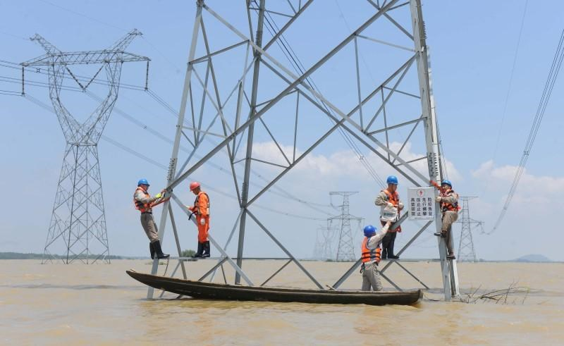 Workers reinforce the electric pylons at a flooded area as Typhoon Nepartak approaches in Xuancheng, Anhui Province, China, July 9, 2016.