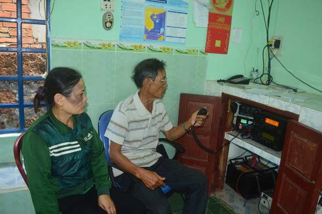 Nguyen Thi Nang sits next to a radio operator, waiting for news from her husband, captain Vo Van Luu, after his boat was reportedly sunk by Chinese vessels in the East Sea.