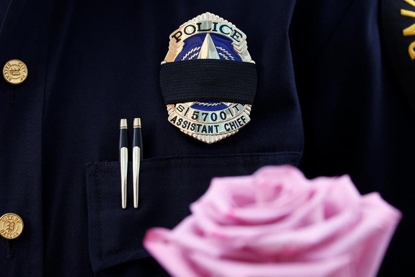 A Dallas Police wears a mourning band as he pays respects at a makeshift memorial at Dallas Police Headquarters following the multiple police shootings in Dallas, Texas, U.S., July 9, 2016.