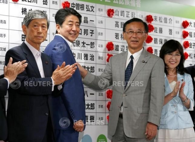 Japan's Prime Minister Shinzo Abe (2nd L), who is also leader of the ruling Liberal Democratic Party (LDP), smiles with LDP policy chief Tomomi Inada (R), Secretary-General Sadakazu Tanigaki (2nd R) and Vice-President Masahiko Komura