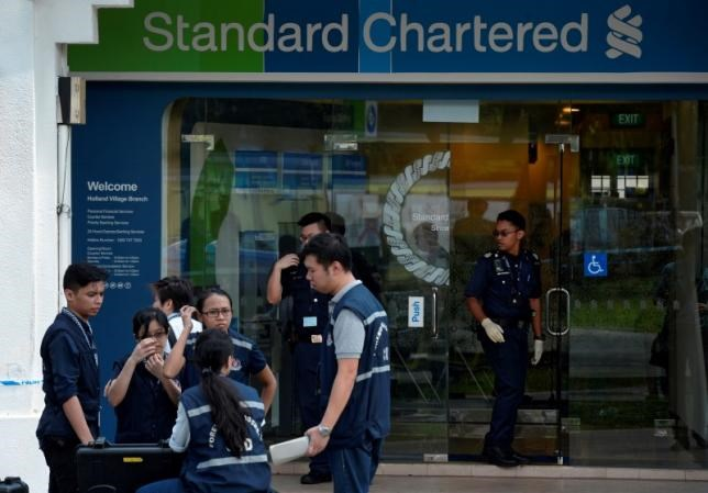 Police officers work at scene of a robbery at Standard Chartered Bank branch in Holland Village, Singapore July 7, 2016. Picture taken July 7, 2016. Straits Times/Mark Cheong/via REUTERS