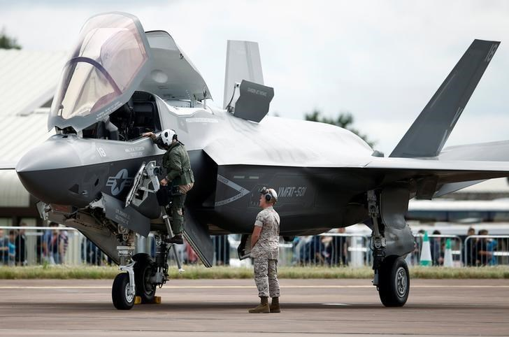 A pilot climbs down from the cockpit of a US Marine Corps Lockheed Martin F-35B fighter jet.