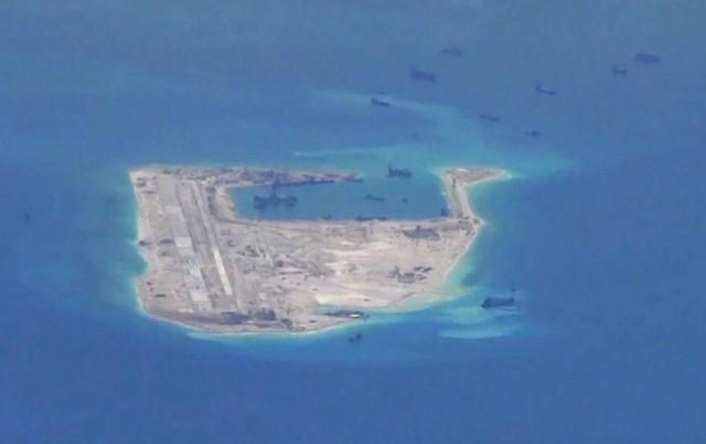 Chinese dredging vessels are purportedly seen in the waters around Fiery Cross Reef in the disputed Spratly Islands in this still image from video taken by a P-8A Poseidon surveillance aircraft May 21, 2015.