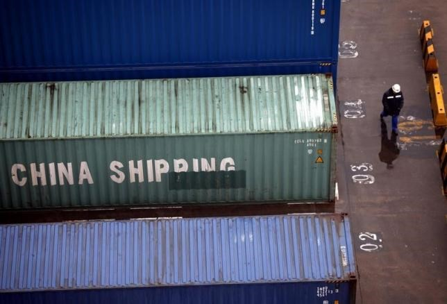 A worker walks past shipping containers at the Port of Shanghai January 19, 2011.