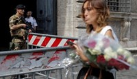 A woman holds flowers to pay tribute to the victims of the Bastille Day truck attack in Nice in front of the French embassy in Rome, Italy, July 15, 2016.