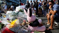 People gather near flowers, candles and a stuffed toy as they pay tribute near the scene where a truck ran into a crowd at high speed killing scores and injuring more who were celebrating the Bastille Day national holiday, in Nice, France, July 15, 2016.