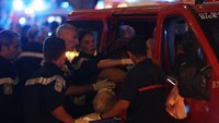 Rescue workers help injured people to get in a ambulance on July 15, 2016, after a truck drove into a crowd watching a fireworks display in the French Riviera town of Nice