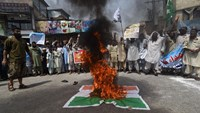 Pakistani supporters of banned organisation Jamaat-ud-Dawa (JuD) shout slogans alongside burning Indian flags during a protest to denounce recent violence by Indian security forces in Indian-administered Kashmir, in Peshawar on July 15, 2016