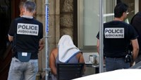 A man covered with a towel is apprehended by French police as the investigation continues two days after an attack by the driver of a heavy truck who ran into a crowd on Bastille Day killing scores and injuring as many on the Promenade des Anglais, in Nice, France, July 16, 2016.