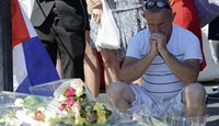 A man reacts by flowers left in tribute to the victims near the scene where a truck ran into a crowd at high speed killing scores and injuring more who were celebrating the Bastille Day national holiday, in Nice, in Nice, July 15, 2016.
