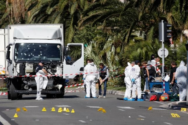 Investigators continue at the scene near the heavy truck that ran into a crowd at high speed killing scores who were celebrating the Bastille Day July 14 national holiday on the Promenade des Anglais in Nice, France, July 15, 2016.
